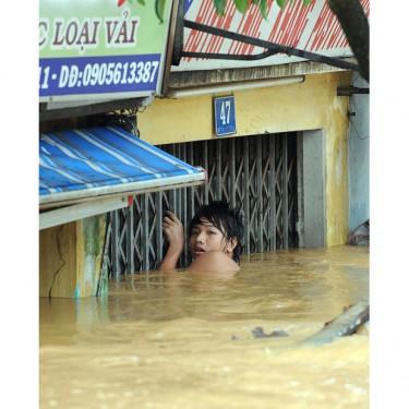 Một thiếu niên bám vào cửa nhà để đi trong biển nước ngập gần tới đầu.