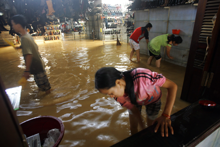 Các nhân viên trong cửa hàng đóng giày, một ngành nghề quen thuộc của phố cổ, múc nước lũ để gột bùn đất sau lũ