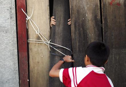 Một người đàn ông cố thủ trong nhà phải nhờ mấy chú nhóc tháo hộ dây buộc bên ngoài.