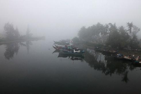 Bến sông vắng lặng trong sương sớm.