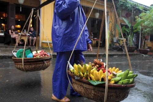 Một người ghánh hoa quả cho khách du lịch thuê chụp ảnh ngơ ngác tìm khách.