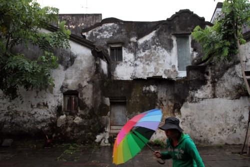 Người phụ nữ đi trong mưa bụi lúc tinh mơ.