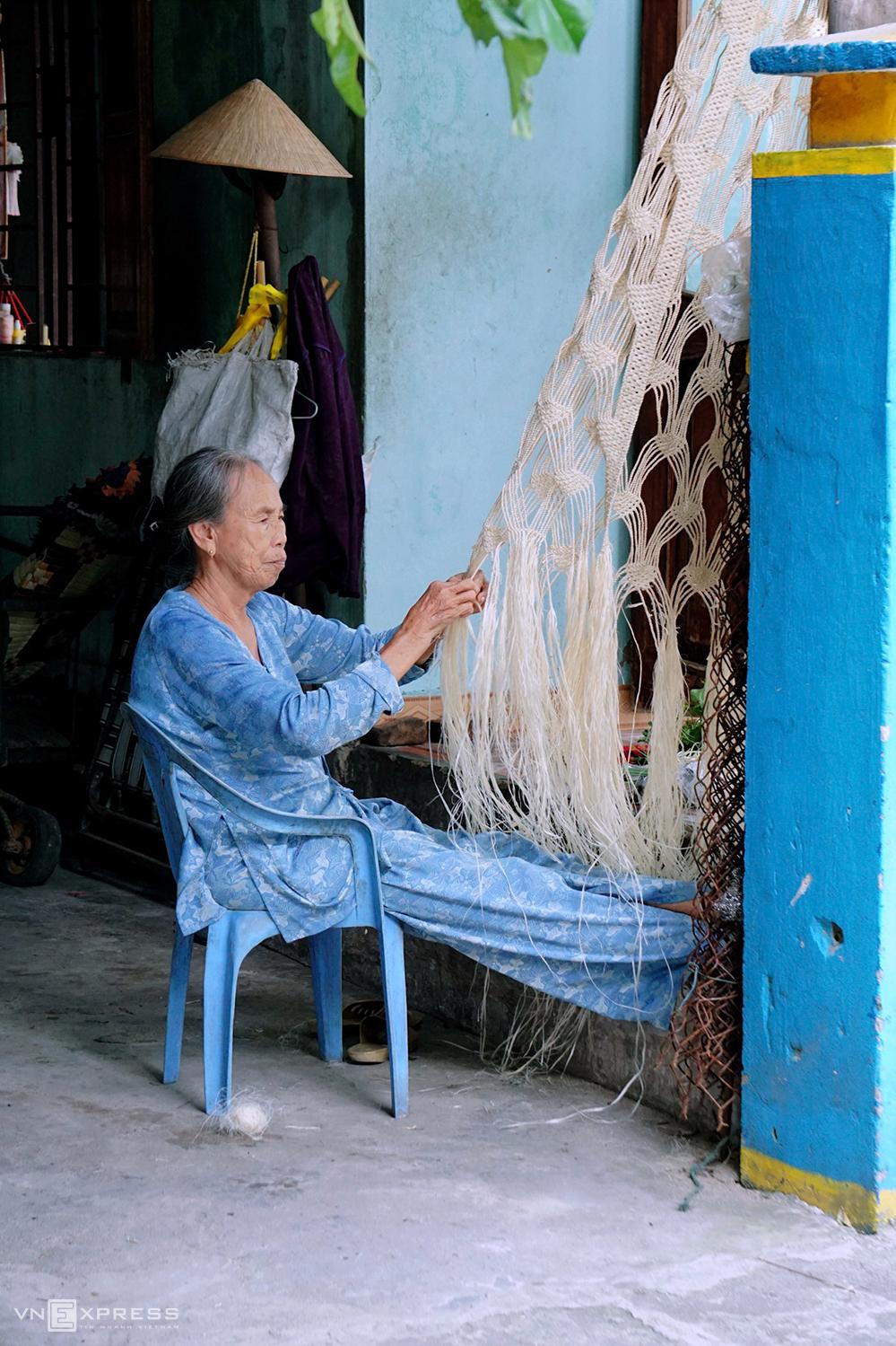Người phụ nữ đan võng từ vỏ cây ngô đồng. Từ khâu bóc tách vỏ cây, đem ngâm nước khoảng chục ngày, đưa về xé sợi mảnh, phơi lấy vài cái nắng giòn mới bắt đầu khâu đan là cả một quá trình, để rồi võng trở thành một trong những món quà lưu niệm có giá trị dành cho khách.