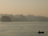 woman-in-boat-at-sunset-with-mountains-ha-long-bay-vietnam